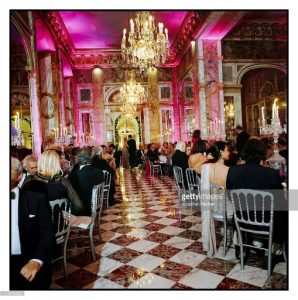 The ostentatious ballroom of marble floors and baroque chandeliers filled with the rich and powerful seated for dinner